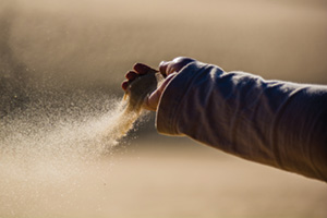 Sand pouring out of someones hand