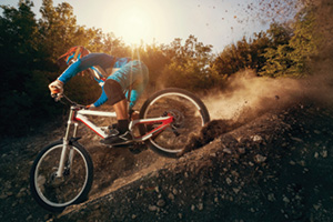 Mountain biker going downhill and kicking up mud