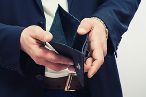 Business man checking wallet which appears to be empty