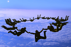 Sky diving team holding hands whilst sky diving