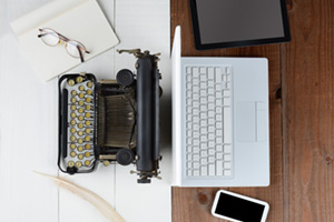 Typewriter and laptop back to back to compare