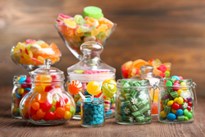 Bunch of colourful sweets in jars on a wooden table
