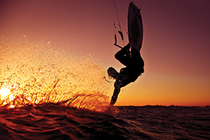 Kite surfer surfing at sunset