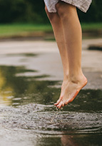 Woman jumping barefoot over a puddle