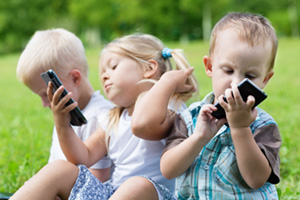Three young children using smartphones whilst sitting in the grass