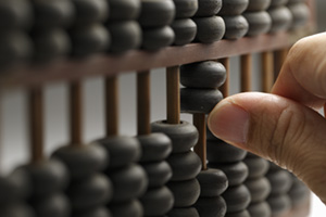Person using old an wooden abacus to calculate