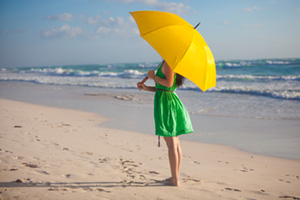 Woman standing on the bun in the sun with her umbrella up