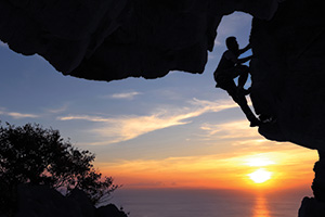 Man climbing side of a cave at sunset