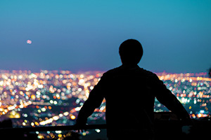 Silhouette of man looking over the city