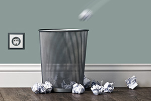 Metal office bin with paper balls being thrown