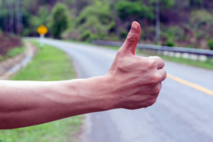 Person holding thumb up to hitchhike