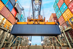 Industrial crane loading containers on a cargo ship