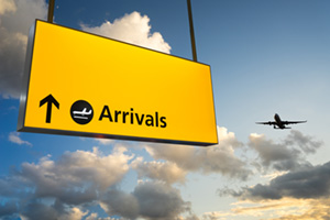 Airport arrival sign with aeroplane in the sky