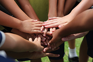 Group of young people putting hands together to display team