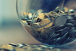 Coins spilling out a piggy bank vase