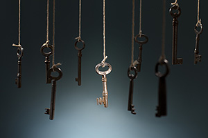 Old keys hanging from ceiling with one key in the spotlight