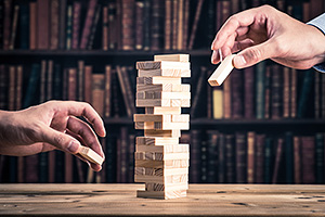 Two people playing Jenga in a library