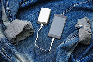 Phone being charged by charger pack ontop of a denim jacket