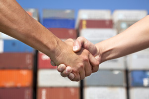 Business men handshaking in front of a stack of containers