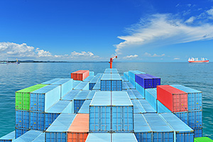 Containers traveling on sea under blue sky