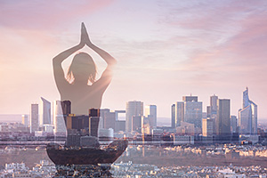 Woman doing yoga with city scape in the background
