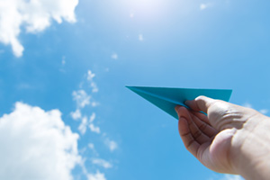 Person launching paper plane into the sky