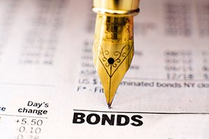 Old fashioned fountain pen pointing at bonds