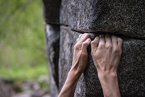 Hands gripping a rock ledge, holding themselves up