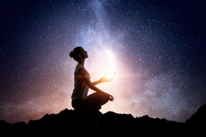 Silhouette of a woman sat in a crossed-legged Yoga pose against a glowing star field.