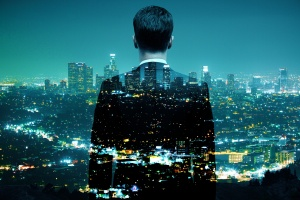 Translucent back of a suited businessman looking out across a night time cityscape