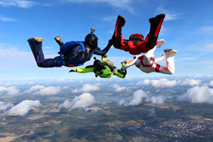 Four skydivers holding onto each other as they fall through the sky