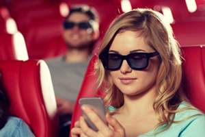 Woman texting during 3D movie in cinema