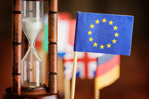 Paper EU flag next to sand timer