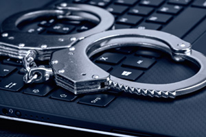 Handcuffs on top of a laptop keyboard to warn off cyber criminals