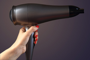 Hairdryer in womans hand with red nails