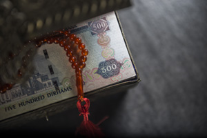 Close up of AED 500 notes in a vintage treasury box with islamic rosary