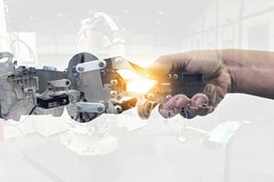 Human hand shaking a robotic hand