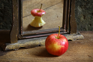 Full bodied apple looking into the mirror, seeing an eaten apple