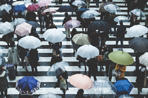 People walking across a crosswalk on a rainy day in Asia