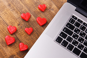Small red heart sweets next to laptop