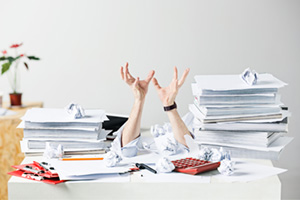 Frustated person in the middle of mountains of paper work