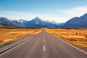Long straight road leading towards snowy mountains