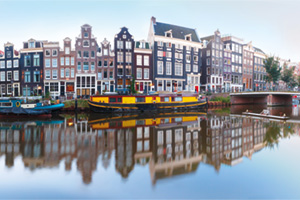 Panorama of Amsterdam canal Singel with typical dutch houses, bridge and houseboats during morning blue hour, Holland, Netherlands