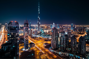 Fantastic rooftop view of Dubai's modern architecture by night with illuminated skyscrapers