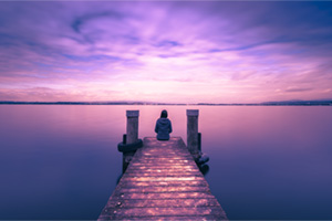Person sitting at the edge of a beach bridge, deep in thought and self reflection