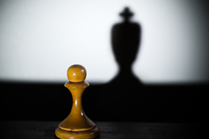Chess pawn casting a king piece shadow in dark concept of strength and aspirations