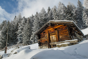 Winter landscape with an old wooden cottage in the swiss alps