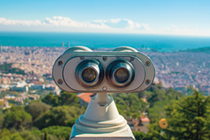 Coin operated binoculars looking over view of a city