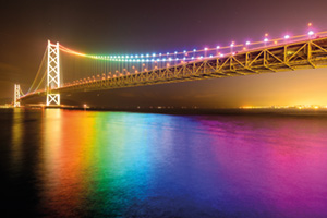 Rainbow lights reflecting in the water off of bridge