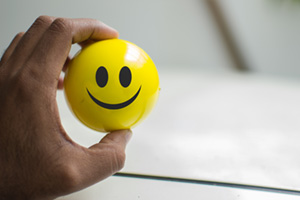 Person holding a yellow ball with a happy face on it